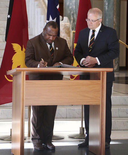 Papua New Guinea's Prime Minister James Marape, left, signs the visitors' book at Australia's Parliament House in Canberra watched by Australian Prime Minister Scott Morrison Monday, July 22, 2019. Marape says his country's relationship with China in not open to discussion during his current visit to Australia. (AP Photograph/Rod McGuirk)