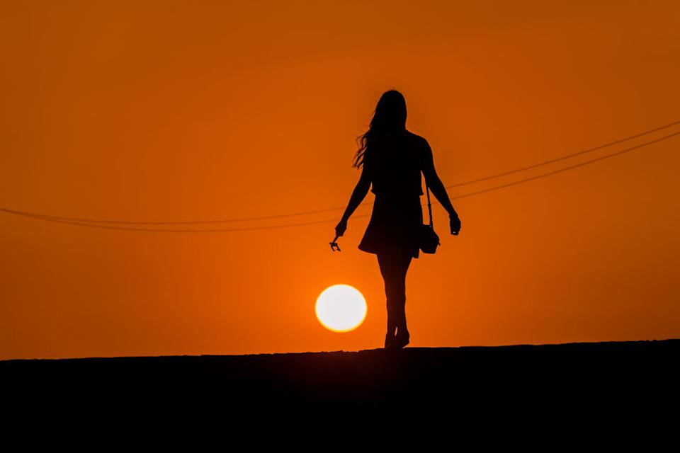 The silhouette of a woman walking on a road as the sun sets. Source: Getty