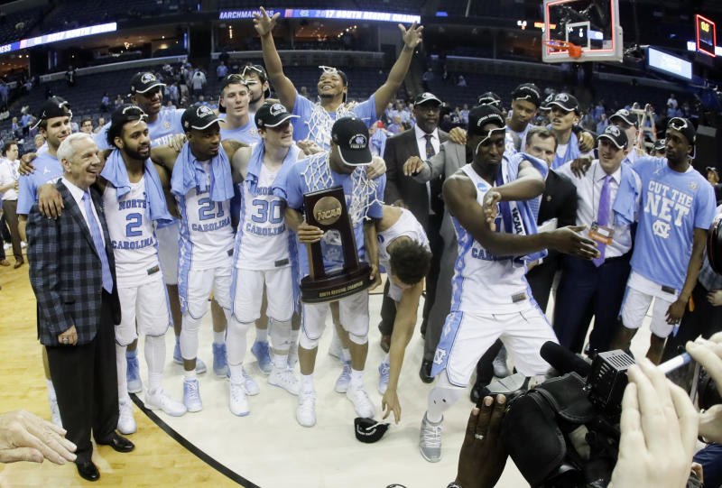 North Carolina players and coaches celebrate after beating Kentucky 75-73 to win the South Regional final game in the NCAA college basketball tournament Sunday, March 26, 2017, in Memphis, Tenn. (AP Photo/Mark Humphrey)