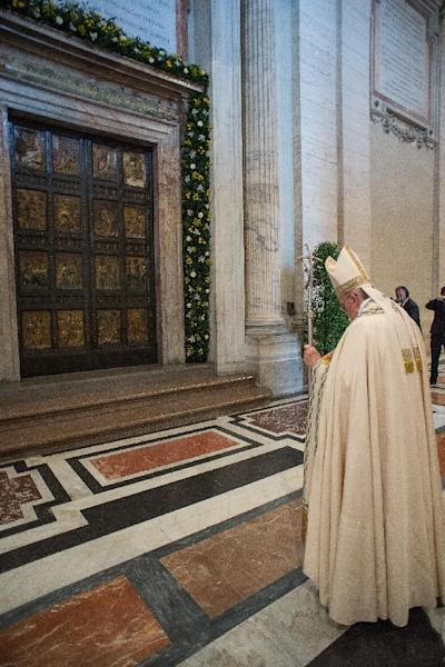 "Pope Francis stands in front of the bronze Holy Door of St Peter's basilica during a ceremony in which the pontiff proclaimed an ""Extraordinary Jubilee of Mercy"" Holy Year, on April 11, 2015 at the Vatican (AFP Photo/)"