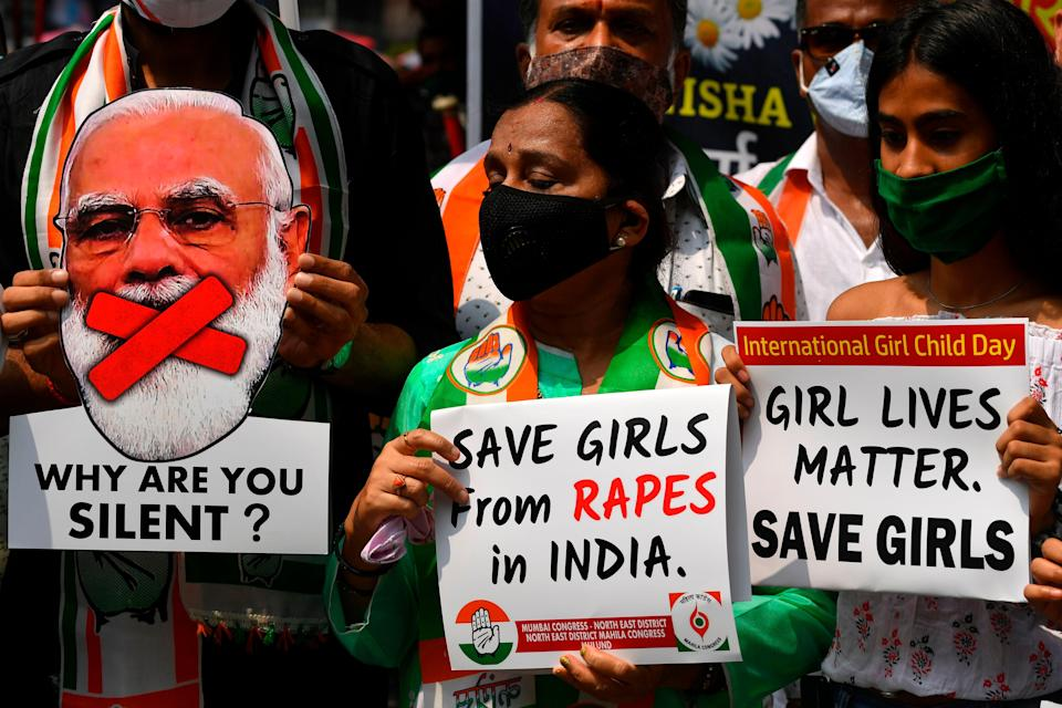 File: Political activists hold placards and a cut-out of India's prime minister Narendra Modi during a protest condemning the alleged gang-rape and murder of a teenaged woman at Hathras in Uttar Pradesh state (AFP via Getty Images)