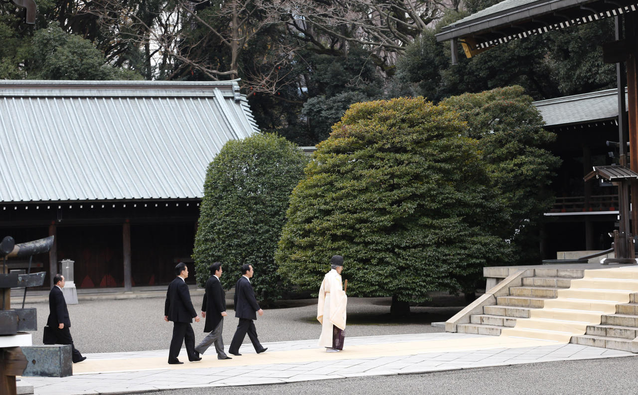 """Japanese Prime Minister Shinzo Abe, third from right, follows a Shinto priest, right, to pay respect for the war dead at Yasukuni Shrine in Tokyo Thursday, Dec. 26, 2013. Abe visited Yasukuni war shrine in a move sure to infuriate China and South Korea. The visit to the shrine, which honors 2.5 million war dead including convicted class A war criminals, appears to be a departure from Abe's """"pragmatic"""" approach to foreign policy, in which he tried to avoid alienating neighboring countries. It was the first visit by a sitting prime minister since Junichiro Koizumi went to mark the end of World War II in 2006. (AP Photo/Shizuo Kambayashi)"""