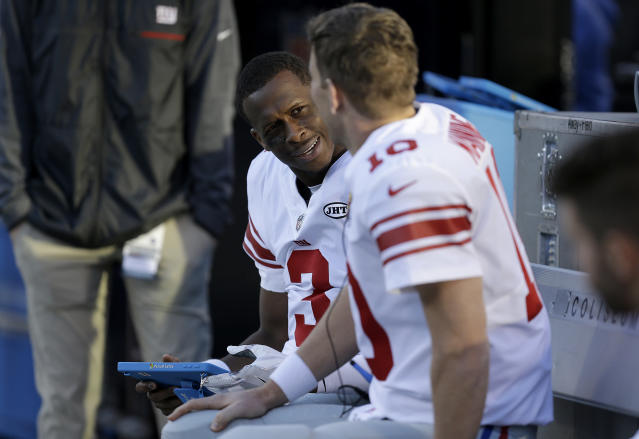 Giants quarterback Geno Smith (L) talks with quarterback Eli Manning during the second half of New York's game against the Oakland Raiders. (AP)