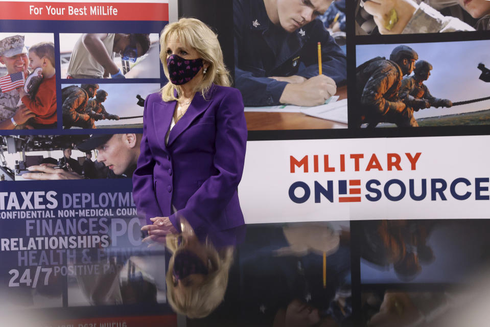 First lady Jill Biden points to a military service member pictured on a sign as she tours Military One Source, an active duty military resource hub/call center for service members, their family and survivors, in Arlington, Va, in Wednesday, April 7, 2021. In announcing the relaunch of Joining Forces, Biden said the initiative will focus on employment and entrepreneurship opportunities for military families, education for the more than 2 million children of enlisted parents and veterans, and the overall health and well-being of these families (Tom Brenner/Pool via AP)