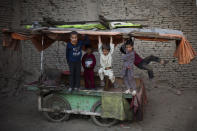FILE - In this Oct. 31, 2010 file photo, children play on a market cart in the old part of Kabul, Afghanistan. (AP Photo/Rodrigo Abd, File)
