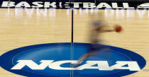 FILE - In this March 14, 2012, file photo, a player runs across the NCAA logo during practice in Pittsburgh before an NCAA tournament college basketball game. The Associated Press has learned that the NCAA has not tested players for performance-enhancing drugs while theyve been at March Madness and other recent college championships. Three people familiar with testing protocols tell AP full-scale testing has not resumed since the coronavirus pandemic shut down college sports a year ago. (AP Photo/Keith Srakocic, File)