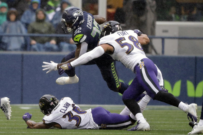 Seattle Seahawks running back Chris Carson (32) leaps over Baltimore Ravens defensive back Chuck Clark, lower left, and tries to avoid Ravens' L.J. Fort (58) during the first half of an NFL football game, Sunday, Oct. 20, 2019, in Seattle. (AP Photo/Elaine Thompson)