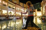 A man wearing a face mask and a face shield as a protection against the coronavirus disease (COVID-19) rows a gondola at a float-in cinema, in Venice Grand Canal Mall, Taguig City, Metro Manila
