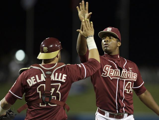 Florida State catcher Danny De La Calle (13) exchanges high-fives with pitcher Jameis Winston (44) after defeating Virginia 6-4 in the Atlantic Coast Conference college baseball tournament in Greensboro, N.C., Saturday, May 24, 2014. (AP Photo/Bob Leverone)