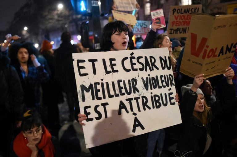 """A protester holds a sign reading """"And the Cesar award for best rapist goes to..."""" during a demonstration in Paris on February 28 last year as guests arrived for the 45th edition of the Cesar Film Awards ceremony"""