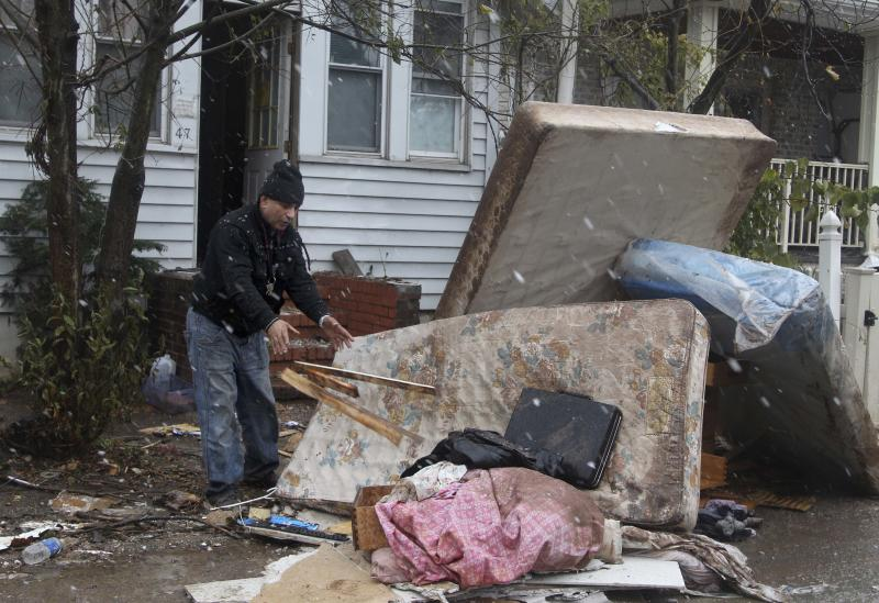 Eddie Saman cleans out his house, which was damaged by Superstorm Sandy, as it begins to snow in the New Dorp section of Staten Island, New York, Wednesday, Nov. 7, 2012. Uncounted numbers of families have returned to coastal homes that are contaminated with mold, which can aggravate allergies and leave people perpetually wheezing. Others have been sleeping in houses filled with construction dust, as workers have ripped out walls and flooring. That dust can sometimes trigger asthma. (AP Photo/Seth Wenig)