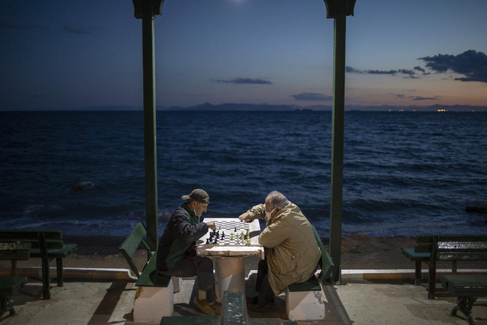 Two men wearing protective face masks play chess in Alimos, a seaside suburb of Athens, on Tuesday, April 20, 2021. (AP Photo/Petros Giannakouris)