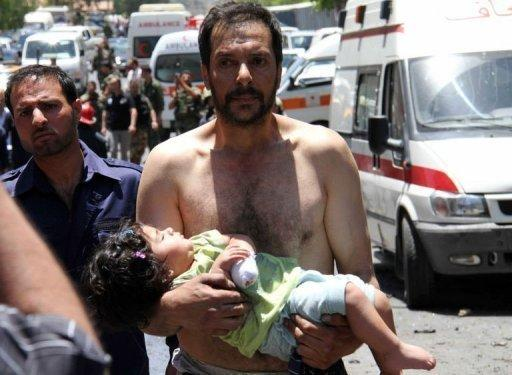 A Syrian man carries a wounded girl next to following an explosion that targeted a military bus near the Qudssaya neighbourhood in the Syrian capital Damascus. UN monitors have finally reached the site of a new massacre in Syria at a second attempt, activists said, as Western powers pressed at the United Nations for sanctions against Damascus