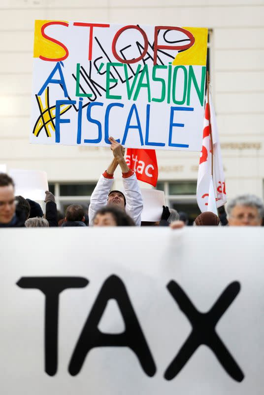 """FILE PHOTO: A man holds a placard reading """"Stop tax avoidance"""" during a protest outside the courthouse ahead of the LuxLeaks trial before an appeal court in Luxembourg"""
