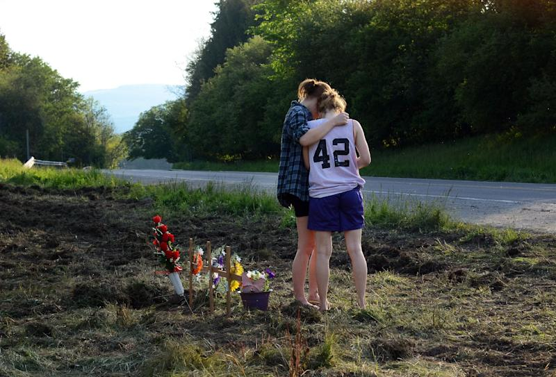Two young women embrace after leaving a rose wreath at the site of the fatal car crash that killed seven along Route 13 in Truxton, N.Y., Thursday, May 30, 2013. Four children and three adults were killed when their minivan was hit by a trailer that became disconnected from it's hitch. The trailer slammed into a minivan with eight people inside. Four children under the age of 10 and three adults in their early 20s were killed. One man survived the crash. (AP Photo/Heather Ainsworth)
