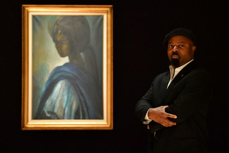 """Nigerian author Ben Okri poses with a work of art by Nigerian painter and sculptor Ben Enwonwu entitled 'Tutu', the """"African Mona Lisa"""" sold at auction in London for £1.2 million (1.4 million euros, $1.7 million), setting a record for the artist"""