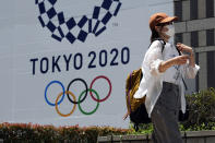 FILE - In this Tuesday, July 20, 2021, file photo, a woman wearing a protective mask walks in front of a Tokyo 2020 Summer Olympics display at the Tokyo Metropolitan government in Tokyo. The Tokyo Olympics have already broken new ground because of the 12-month delay caused by the coronavirus pandemic, pushing it into an odd-numbered year for the first time. But with no fans permitted in Japan, foreign or local, it has the undesirable distinction of being the first Games to be held with no spectators. (AP Photo/Kiichiro Sato, File)