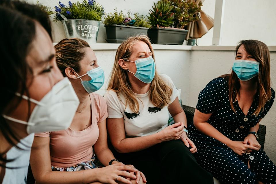 Group of friends hanging out wearing masks