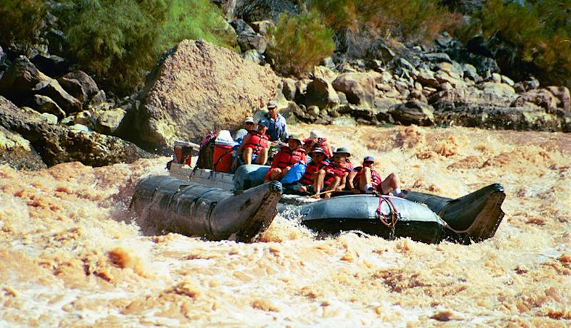 FILE - This Aug. 31, 2002 file photo shows a group of visitors riding a pontoon raft through rapids in Grand Canyon National Park, Ariz. Thousands of people who had been on a waiting list for a coveted trip on the Colorado River through the Grand Canyon still are waiting. (AP Photo/Brian Witte, File)