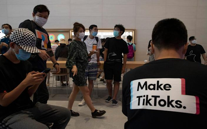 """A visitor to an Apple store wears a T-shirt promoting Tik Tok in Beijing. Nigel Inkster, a former intelligence and operations director at the UK's Secret Intelligence Service, said the Beijing-owned app could serve as an """"entry-point"""" for Chinese hackers - Ng Han Guan/AP"""