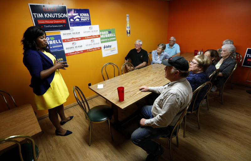 In this Wednesday, Oct. 3, 2018 photo, Iowa Democratic candidate for secretary of state Deidre DeJear, left, talks to local residents during a campaign stop in Osage, Iowa. DeJear is an example, perhaps the best, of Democrats around the country fighting for this lesser-known statewide office in 2018 over what has been a steady tightening of voting rules in states under Republican leadership. (AP Photo/Charlie Neibergall)