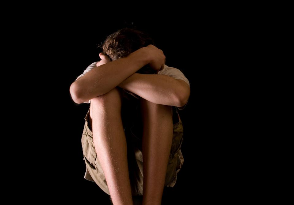 Young teenage boy crouches against dark background.