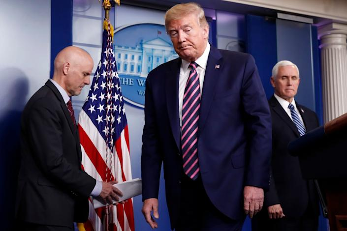 Donald Trump at a White House briefing on the coronavirus pandemic with Stephen Hahn, left, commissioner of the US Food and Drug Administration, and Vice-President Mike Pence: AP