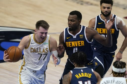 Dallas Mavericks' Luka Doncic (77) moves to the basket against Denver Nuggets guard Gary Harris, bottom center, Paul Millsap (4) and Jamal Murray, right, in the first half of an NBA basketball game in Dallas, Monday, Jan. 25, 2021. (AP Photo/Tony Gutierrez)