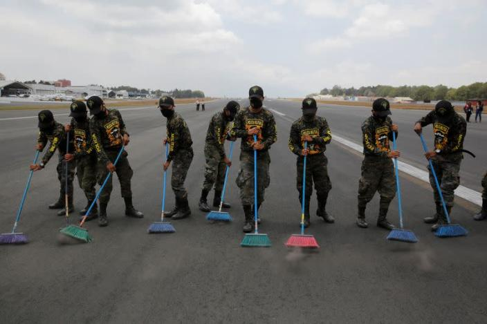 FILE PHOTO: Soldiers sweep volcanic ashes at La Aurora International Airport in Guatemala City
