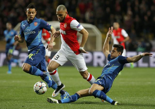 AS Monaco's Layvin Kurzawa (C) makes his way through Arsenal's Francis Coquelin (L) and Alexis Sanchez (R) during their Champions League round of 16 second leg soccer match at the Louis II Stadium in Monaco, March 17, 2015. REUTERS/Eric Gaillard (MONACO - Tags: SPORT SOCCER)