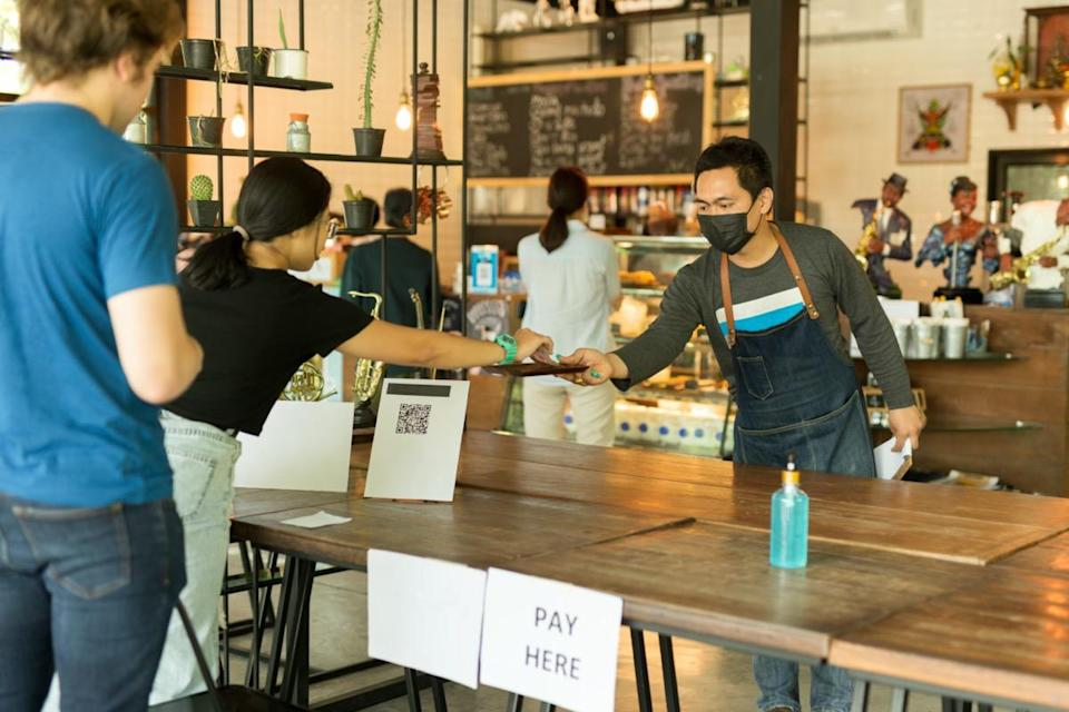 Social distance conceptual small business waiter serving customer in cafe.