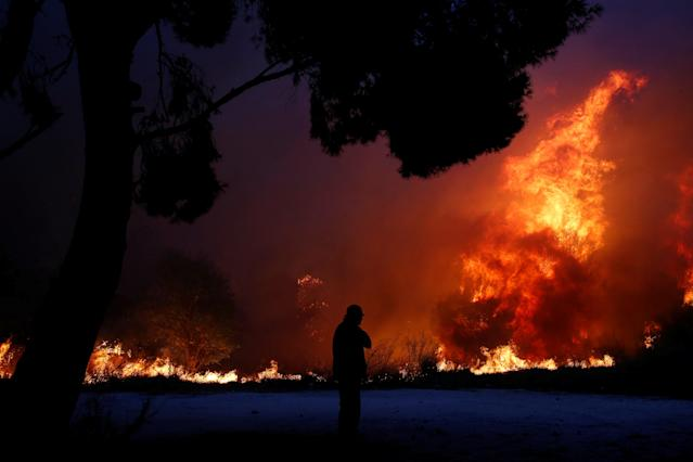 <p>A man looks at the flames as a wildfire burns in the town of Rafina, near Athens, Greece, July 23, 2018. (Photo: Costas Baltas/Reuters) </p>