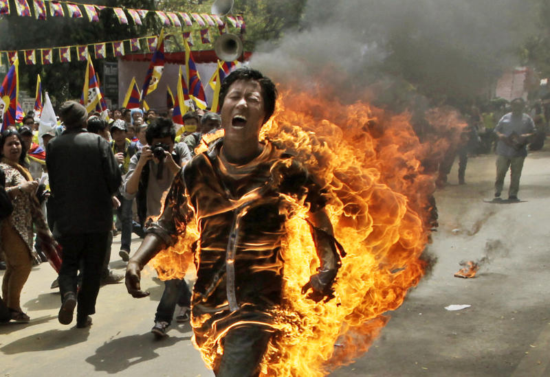 A Tibetan man screams as he runs engulfed in flames after self-immolating at a protest in New Delhi, ahead of Chinese President Hu Jintao's visit to the country Monday, March 26, 2012. The Tibetan activist lit himself on fire at the gathering and was rushed to hospital with unknown injuries, reports said. (AP Photo/Manish Swarup)