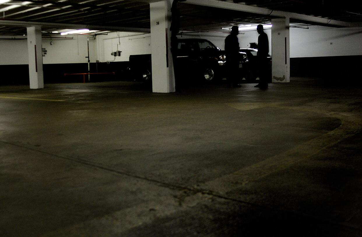 ROSSLYN, UNITED STATES: A reporter (R) confers with a man in the shadows next to column 32 on D floor of the garage at 1401 Wilson Blvd 01 July 2005 in Rosslyn, VA, where Washington Post reporter Bob Woodward had his clandestine meetings with former FBI official Mark Felt, otherwise know as 'Deep Throat', the secret source in the Watergate scandal that brought down the presidency of Richard M. Nixon in 1974. Following the sudden revelation of Deep Throat's identity in April 2005, Woodward, now an assistant managing editor at the Post, has authored a new book, 'The Secret Man', slated for release 06 July 2005. AFP PHOTO/Jim WATSON (Photo credit should read JIM WATSON/AFP/Getty Images)