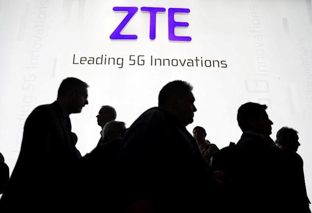 Visitors pass in front of the Chinese telecoms equipment group ZTE Corp booth at the Mobile World Congress in Barcelona, Spain, February 26, 2018. REUTERS/Sergio Perez/Files