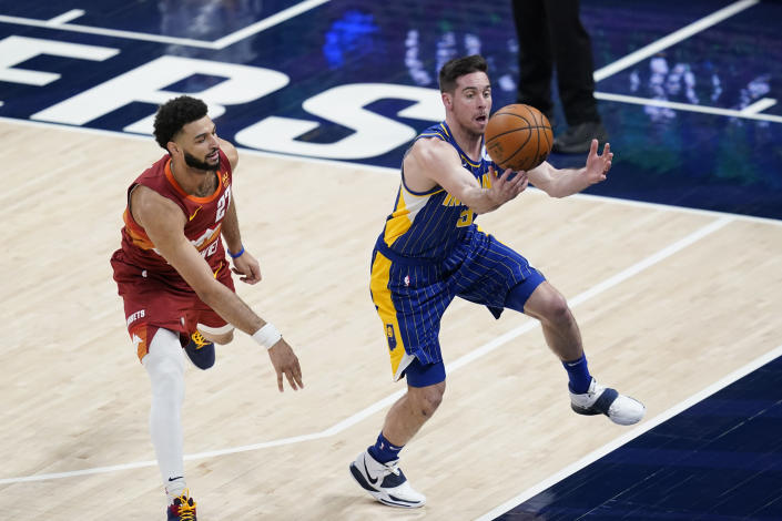 Indiana Pacers' T.J. McConnell (9) tries to steal the ball from Denver Nuggets' Jamal Murray (27) during the first half of an NBA basketball game, Thursday, March 4, 2021, in Indianapolis. (AP Photo/Darron Cummings)