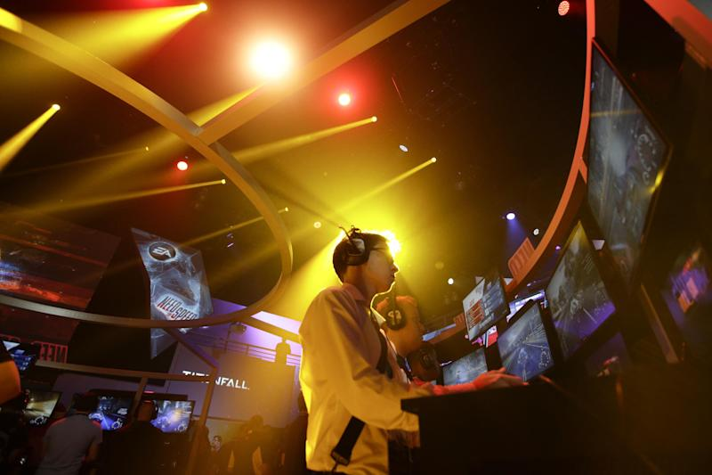 """Frank Cire, center, plays the """"Need for Speed"""" racing video game at the EA booth during the Electronic Entertainment Expo in Los Angeles, Wednesday, June 12, 2013. (AP Photo/Jae C. Hong)"""