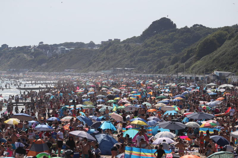 People are seen on the beach on the hottest day of the year, after an easing of social restrictions due to coronavirus, in Bournemouth, England, Wednesday, June 24, 2020. Temperatures reached 32.6C (90.7F) at London's Heathrow Airport on Wednesday. (Andrew Matthews/PA via AP)