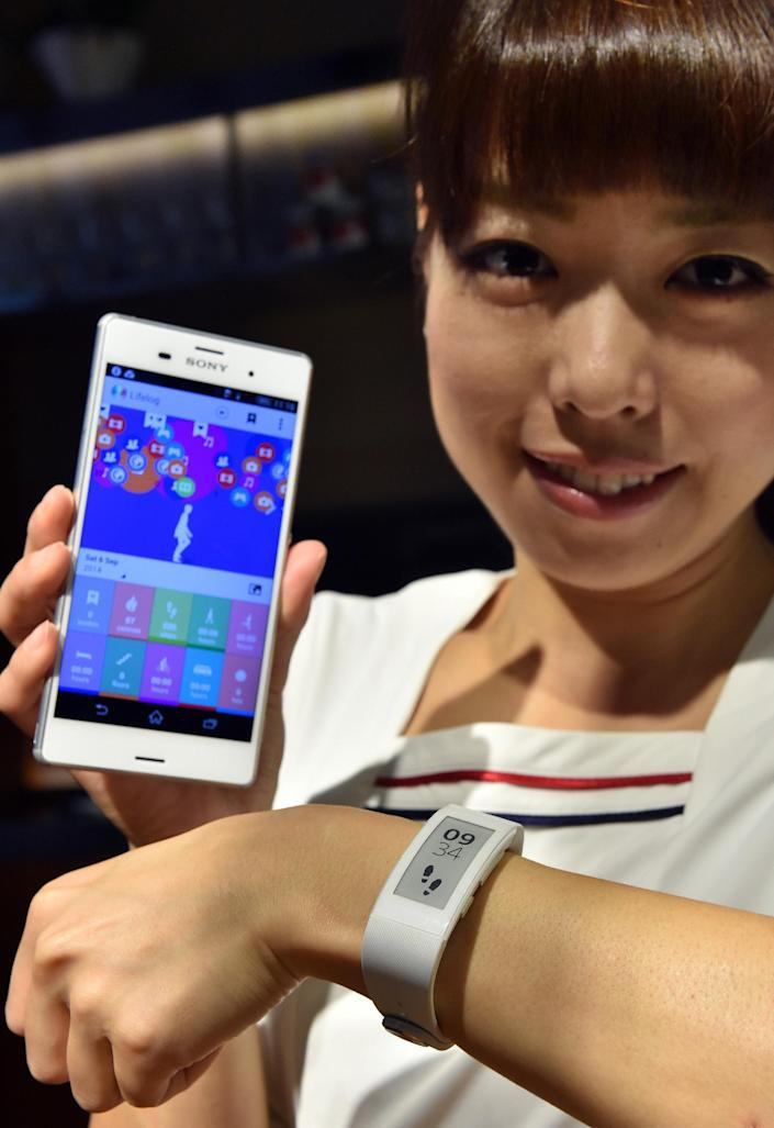 A Sony employee displays the new wristwatch styled smartwear 'SmartBand Talk' and the new smartphone 'Xperia Z3' at the company's headquarters in Tokyo, on September 9, 2014 (AFP Photo/Yoshikazu Tsuno)