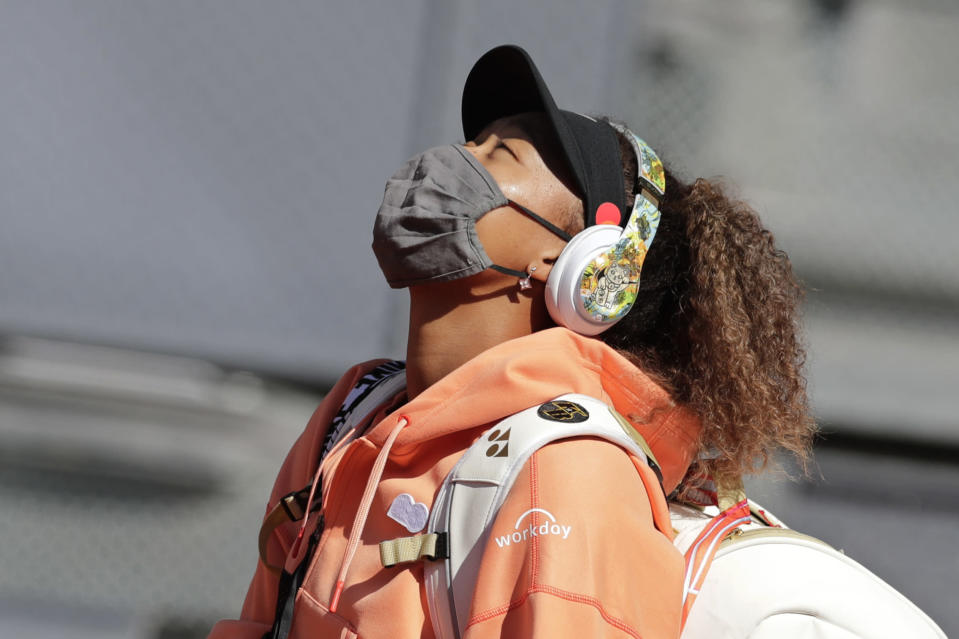 Naomi Osaka of Japan arrives on court for her match against Karolina Muchova of the Czech Republic during their match at the Madrid Open tennis tournament in Madrid, Spain, Sunday, May 2, 2021. (AP Photo/Paul White)