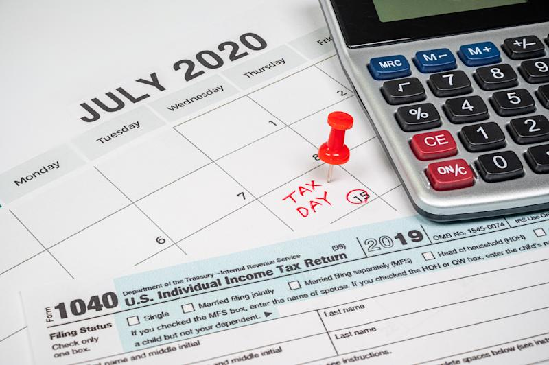The tax day was extended to July 15th because of Covid-19. July calendar showing 1040 return form and tax day