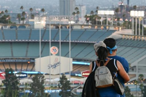 A couple looks out over an empty stadium as the Los Angeles Dodgers play the San Francisco Giants in Los Angeles
