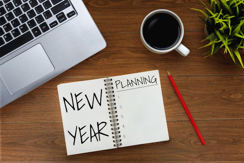 New Year Resolution Goal and Target Setting List 2020 - Business office desk with notebook written in handwriting about plan listing of new year goals and resolutions setting. Change and determination concept.