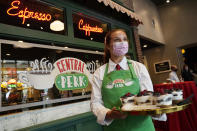 """Madison Lakratz offers chocolate trifles to visitors to the """"Friends""""-inspired """"Central Perk Cafe"""" at the Warner Bros. Studio Tour Hollywood media preview on June 24, 2021, in Burbank, Calif. (AP Photo/Chris Pizzello)"""
