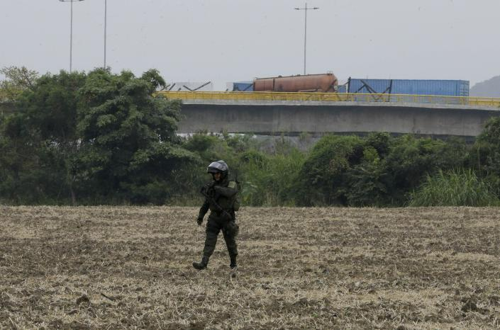 A fuel tanker, cargo trailers and makeshift fencing are used as barricades by Venezuelan authorities attempting to block humanitarian aid entering from Colombia on the Tienditas International Bridge that links the two countries as a Colombian police officer patrols nearby, on the outskirts of Cucuta, Colombia, Wednesday, Feb. 6, 2019. Immigration authorities say the Venezuelan National Guard built the roadblock a day earlier. (AP Photo/Fernando Vergara)