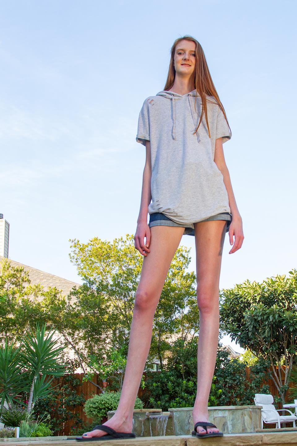 ***EXCLUSIVE VIDEO AVAILABLE*** AUSTIN, TX, USA - 11 AUGUST 2019: 16-year-old Maci Currin, whose 53 inch long legs are believed to be the world's longest, at home on 11 August, 2019, in Austin, Texas. A TOWERING teenager from Texas is about to strut her way into the record books as the proud owner of the world's longest legs. Aged only 16, Maci Currin, from Austin, Texas, has legs measuring an incredible 53 inches - smashing the previous record of 52.2 inches held by Ekaterina Lisina, of Russia. The 6ft 9in aspiring model was only 19 inches when born, but a series of growth spurts meant she rocketed to 5ft 7in by the time she was nine years old. Maci also has an inseam of 43 inches and has to stoop to avoid banging her head when walking through doors, but says she is proud of her lengthy limbs despite the added attention they bring. PHOTOGRAPH BY: Bradley Beesley / Barcroft Media (Photo credit should read Bradley Beesley / Barcroft Media / Barcroft Media via Getty Images)
