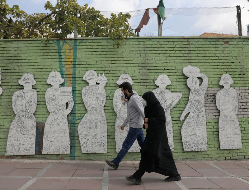 FILE PHOTO: Iranians wearing face masks walk on a street after Iranian authorities made it mandatory for all to wear face masks in public following the outbreak of the coronavirus disease (COVID19), in Tehran Iran October 10, 2020.