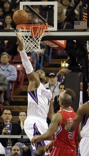 Sacramento Kings center DeMarcus Cousins, left, flips the ball into the basket as Los Angeles Clippers' Caron Butler, left, and Blake Griffin, background, watch during the first quarter of an NBA basketball game in Sacramento, Calif., Thursday, April 5, 2012. (AP Photo/Rich Pedroncelli)