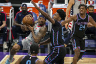 Washington Wizards guard Bradley Beal (3) drives to the basket as he's defended by Sacramento Kings center Damian Jones (15) during the first quarter of an NBA basketball game in Sacramento, Calif., Wednesday, April 14, 2021. (AP Photo/Hector Amezcua)