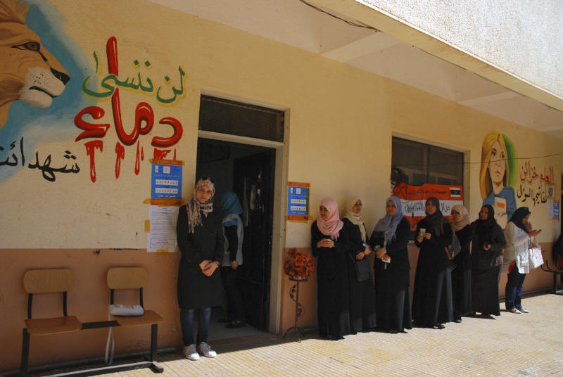 """Libyan voters line up at a polling station in Benghazi, Libya Saturday, July 7, 2012. Jubilant Libyans marked a major step toward democracy after decades of erratic one-man rule, voting Saturday in the first parliamentary election after last year's overthrow and killing of longtime dictator Moammar Gadhafi. But the joy over the historic vote was tempered by boycott calls, the burning of ballots and other violence in Libya's restive east. Arabic at left reads"""" don't forget the blood of the martyrs."""" (AP Photo/Ibrahim Alaguri)"""
